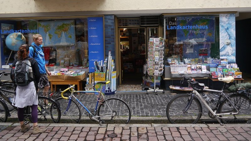 Thomais and Phil with our bikes outside a map shop in Freiburg.