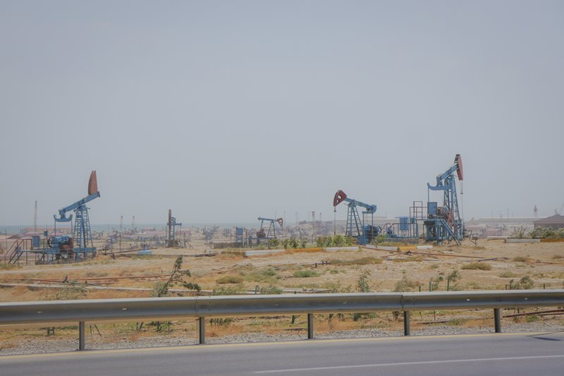 Some rusty oil rigs in Baku atop desert sand