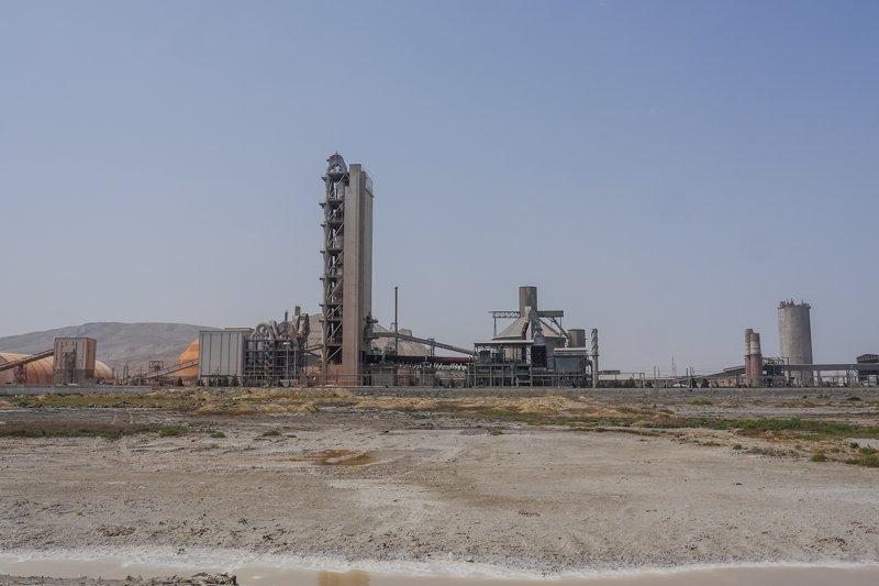 Some rusty factories atop desert sand