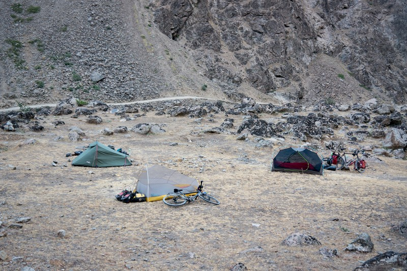 Our 3 tents pitched amongst some rocks in Tajikistan, with Afghanistan in the background