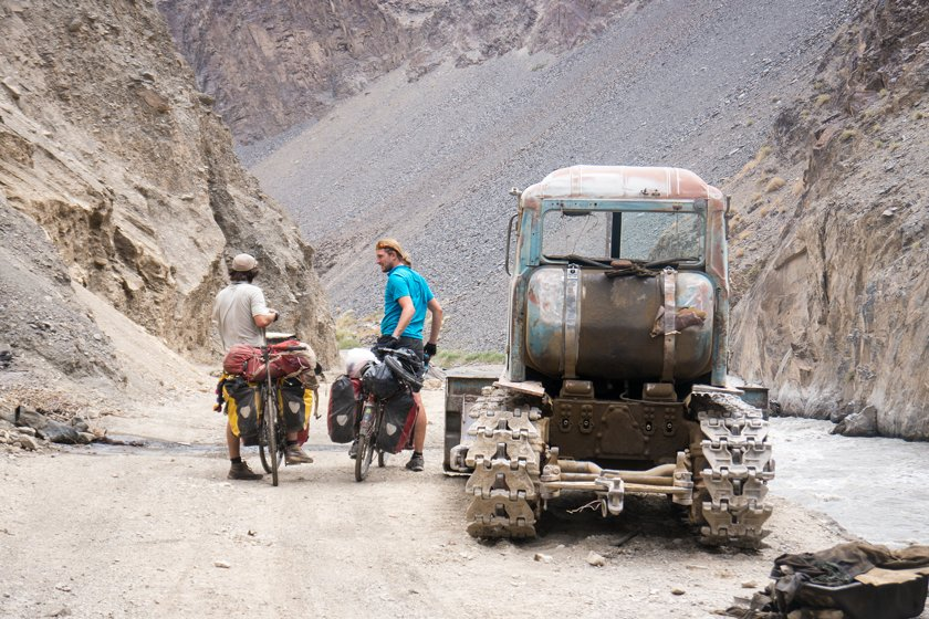 Cyclists next to an old tractor in the Bartang