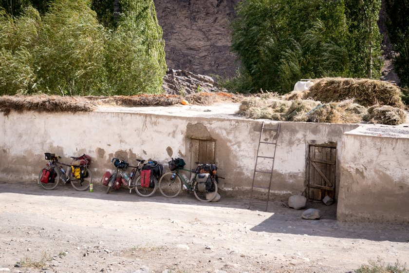Our three touring bicycles next to an old house in the Pamirs, Bartang valley