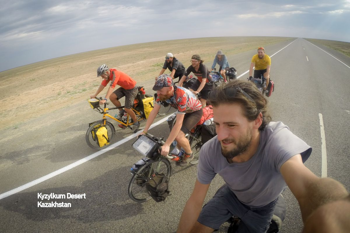 This image shows a group of cyclists in the Kyzylkum desert, Khazakstan