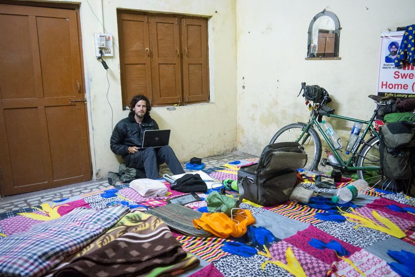 Jamie and his bicycle in a room in India